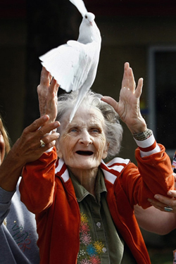 Elderly woman releasing white dove
